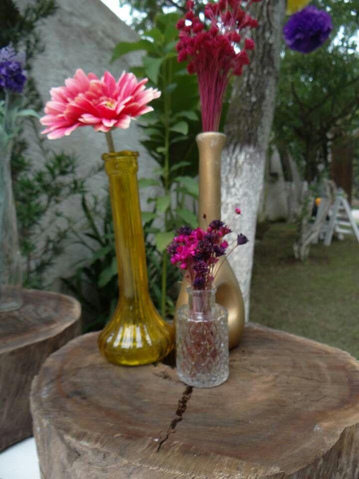 Garrafas com flores sobre fatia de tronco