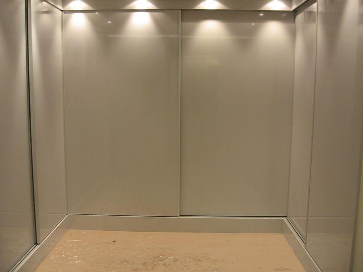 """Vestidor en """"U"""" con puertas lacadas en gris claro."""