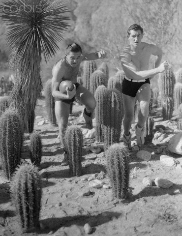 Original caption:California: Aaron Rosenberg and Homer Griffith, University of Southern California Football players, practicing among the Cactus at Palm Springs, California.  January 01, 1933: California Football, Football Players, Palmsprings, Palm Springs, Photo Opportunity, Vintage Photo
