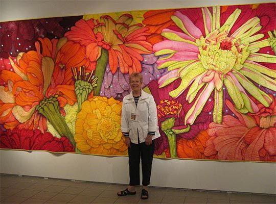 Velda Newman standing in front of her Zinnia quilt. This is one of the most incredible quilts of the century