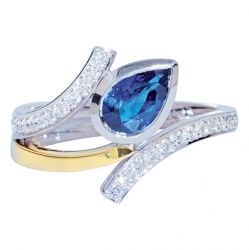 MELODY - FLOWING PEAR SHAPE SAPPHIRE AND DIAMOND RING  An abstract shape was created by angling this luminous blue sapphire amid a cross over of finely hand set diamonds in white gold. A yellow gold feature further enhances this delicate design.