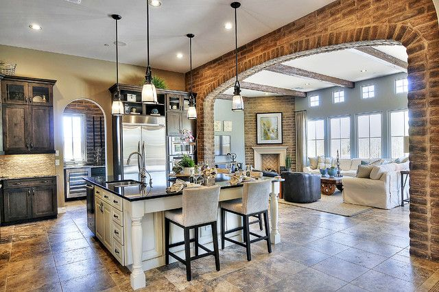 This grand, open kitchen design features a massive square island in white with black countertop, with a large brick arch separating it from the living room beyond. Large format tile flooring and dark wood cabinetry enhances the luxurious feel.