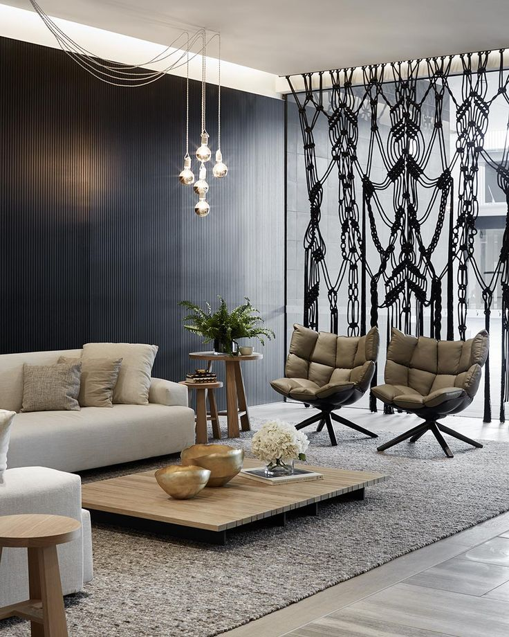 Black Macrame Space Divider Creates An Eye Catching Accent For This Living