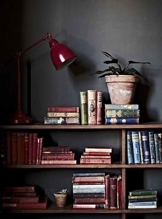 Add a little colour to your room with shelves of coloured books. Why not collect them in warm marsala tones and display in stacks...: