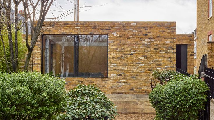 Reclaimed brick walls help this home of modest proportions blend with its historic context in London, where it stands on top of a former prison