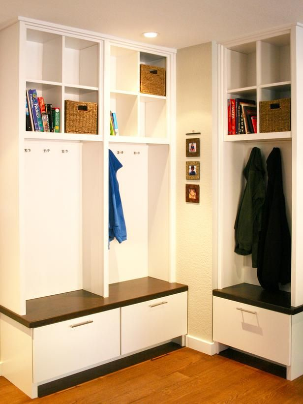 Missing a mudroom? Turn an awkward corner or downstairs dead space into valuable entryway storage. The designer transformed this corner into a makeshift mudroom by adding an L-shaped floor-to-ceiling storage unit. A combination of cubbies, baskets, hooks, bench seating and pullout drawers create the perfect combination of storage to organize everything from scarves to schoolbooks.