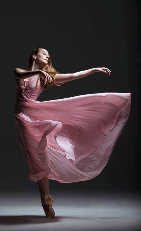 Ballerina dancing point in beautiful pink dress, graceful beauty.