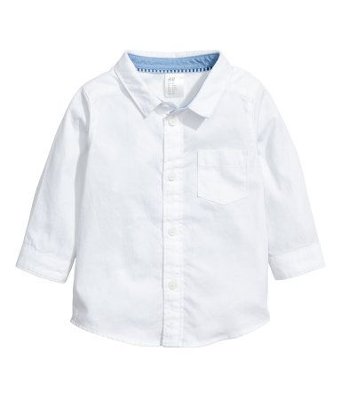 White. Shirt in soft, woven cotton fabric. Collar, buttons at front, chest pocket, and long sleeves with buttons at cuffs. Gently rounded hem.