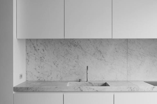 Minimal white kitchen by Nicolas Schuybroek in Brussels. Carrara marble integrated kitchen sink. Plain white 2 pak cabinets.