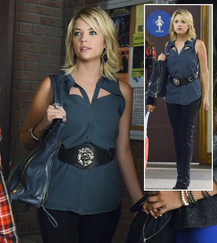 Hanna wearing blue cut out top, detailed black belt, black pants and blue shoulder bag