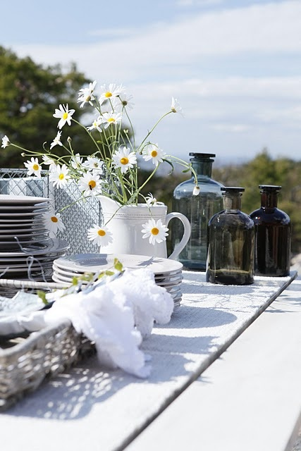 Simple white daisies in pretty white enamelware pitchers will look lovely on the table with the navy & yellows. #designsponge #dssummerparty