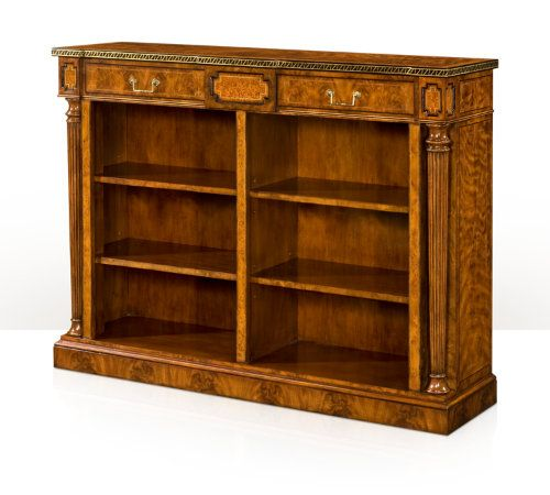 A walnut veneered low open bookcase, the rectangular yew burl crossbanded top with an ebony and brass inlaid edge, the frieze with two drawers flanked by yew burl panels, above two open sections each with two adjustable shelves, flanked by yew burl uprights  and turned and fluted columns, on a plinth base.