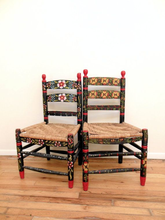 These two Mexican hand painted chairs are impossibly charming with their floral details, rush seats, and minor imperfections. These pieces of Mexican folk art make great hall chairs, cat chairs, bonus chairs for parties, or childrens chairs.  Each primitive wood chair is hand painted in a color combination of black red yellow.  These hand painted chairs are rush seat chairs with minor imperfections in wood and rush. Please see photos.  These folk art chairs are so easy to love. Just set…