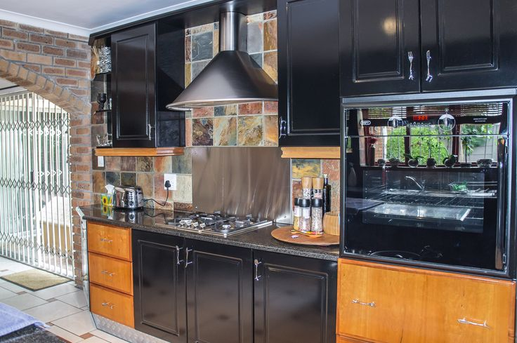 Built-in cupboards and oven with hob and extractor fan in the kitchen of this lovely Paarl home on sale through The Real Estate Avenue.