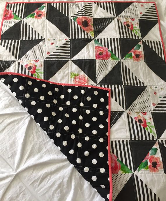This is a beautiful handmade quilt featuring a printed black, white, and floral quilt top with a classic black and white polka-dot backing. The top is modern half-square triangle pattern. It has been machine quilted with White and Natural 100% cotton batting secured inside. The binding is a coral solid fabric that is double folded and hand sewn for a pristine look and durable enough for the toughest love. This quilt is perfect for a stroller, carseat, baby tummy time or snuggling with during…