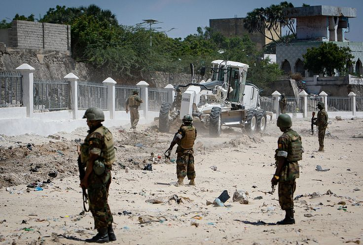 Ugandan soldiers serving with the African Union Mission in Somalia (AMISOM) stand guard while an earth grader  operated by combat engineers clears sand, debris and rubble from an area known as EL-Gabta or 'Peace Gardens' in central Mogadishu. El Gabta will eventually become an open-air park area and gardens for people to use and relax in. AU-UN IST PHOTO / STUART PRICE.