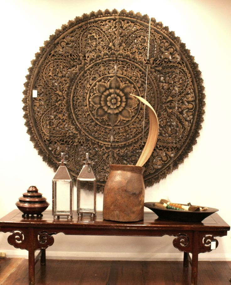 Carved Thai panel and a Chinese bench with hurricane lanterns.