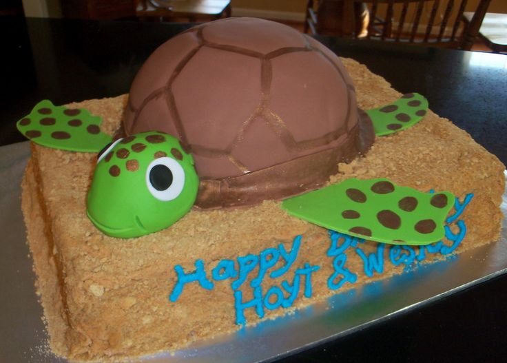 11 X 15 iced in butter cream and covered with crushed graham crackers for sand.  Turtle shell is made from 8 inch round with a ball pan cake on top and both covered in fondant, with fondant head and arms.