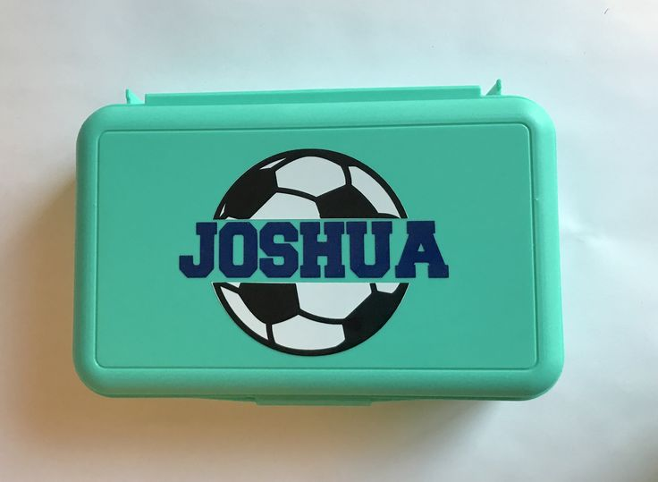 """Our new Personalized Soccer Pencil Box is sure to score a goal with your soccer player!    Our pencil boxes are plastic and we use high quality Oracal 651 vinyl for the design.  They are 8"""" x 4.5"""" x 2.75"""" in size...just the right size to hold your child's pencils, crayons, and more.  We used Dark Blue for the name on an aqua pencil box. Are you interested in a custom pencil box for your child as they start school this fall?  Visit us at www.MamaBforMe.etsy.com today!"""