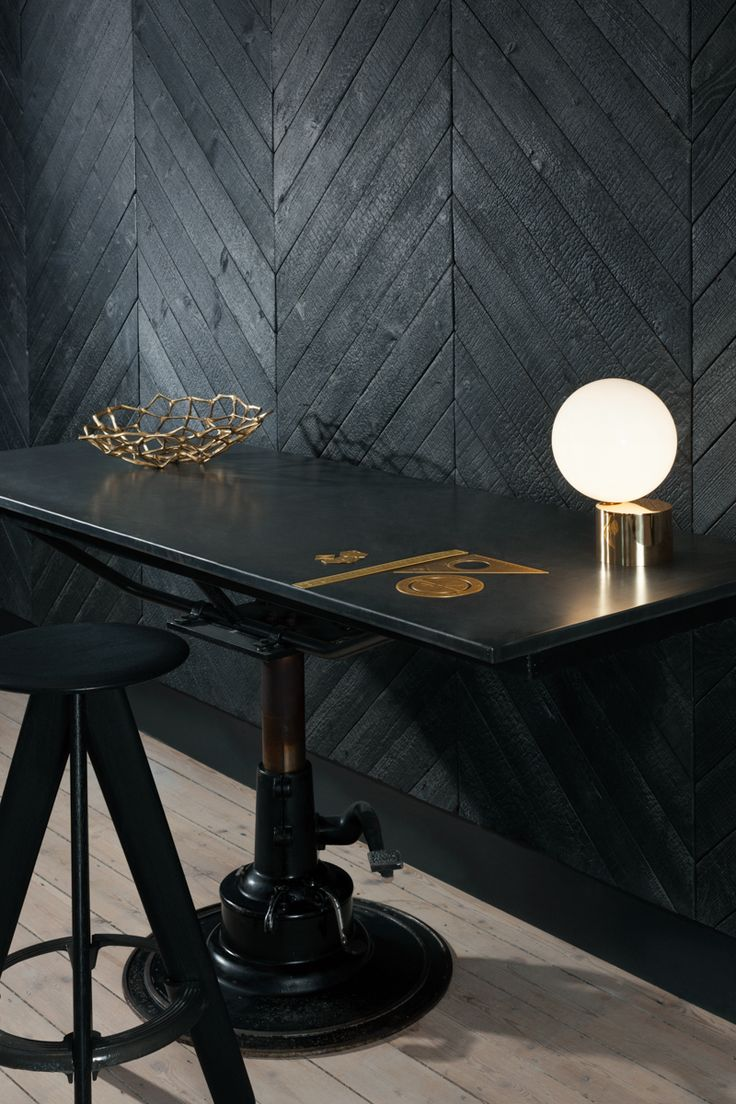 Dark, charred interiors of Metropolitan Wharf by Tom Dixon's Design Research Studio. Featuring a Slab stool and Etch stationery.