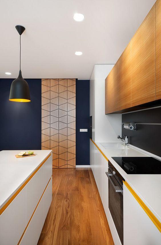 Uma opção para executar a dispensa em um lugar visível da cozinha, é a utilização de painéis ou portas de correr. Nesse exemplo o painel  de madeira desenhado agrega no design do ambiente, e conversa com os tons do armário e do piso, se destacando na parede escura. Visite gouparquitetura.com para mais dicas de arquitetura.