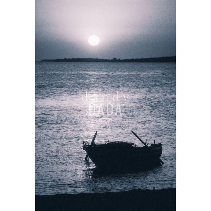 """Moonlight L'opera """"Sailing at the midnight"""" di Alberto Fanelli appartiene alla collezione """"Notturno"""". Le fotografie notturne sanno sempre colpire l'animo di chi le osserva. Bastano solo pochi elementi: il mare, la luna e la sagoma di un peschereccio. L'immagine si concentra nella parte alta del fotogramma; è un climax iperbolico di pathos e ricordi che affollano la mente. Grecia, 2014."""
