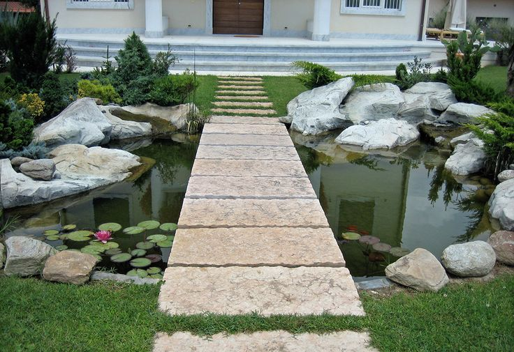 This floating walkway over an entranceway pond was created by Quentin Owen and Antonio Menchini for a client in Toscany, Italy