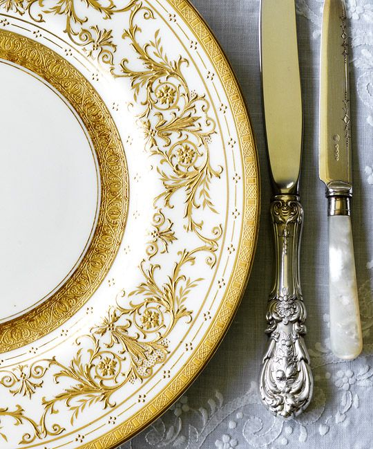 """Raised 22-karat gold scrollwork plates by Minton, circa 1900, with Reed & Barton's ornate """"Francis I"""" knife, a family heirloom. - This is edwardian, which immediately followed Victorian, but celebrated a return to luxury and fun in the court."""