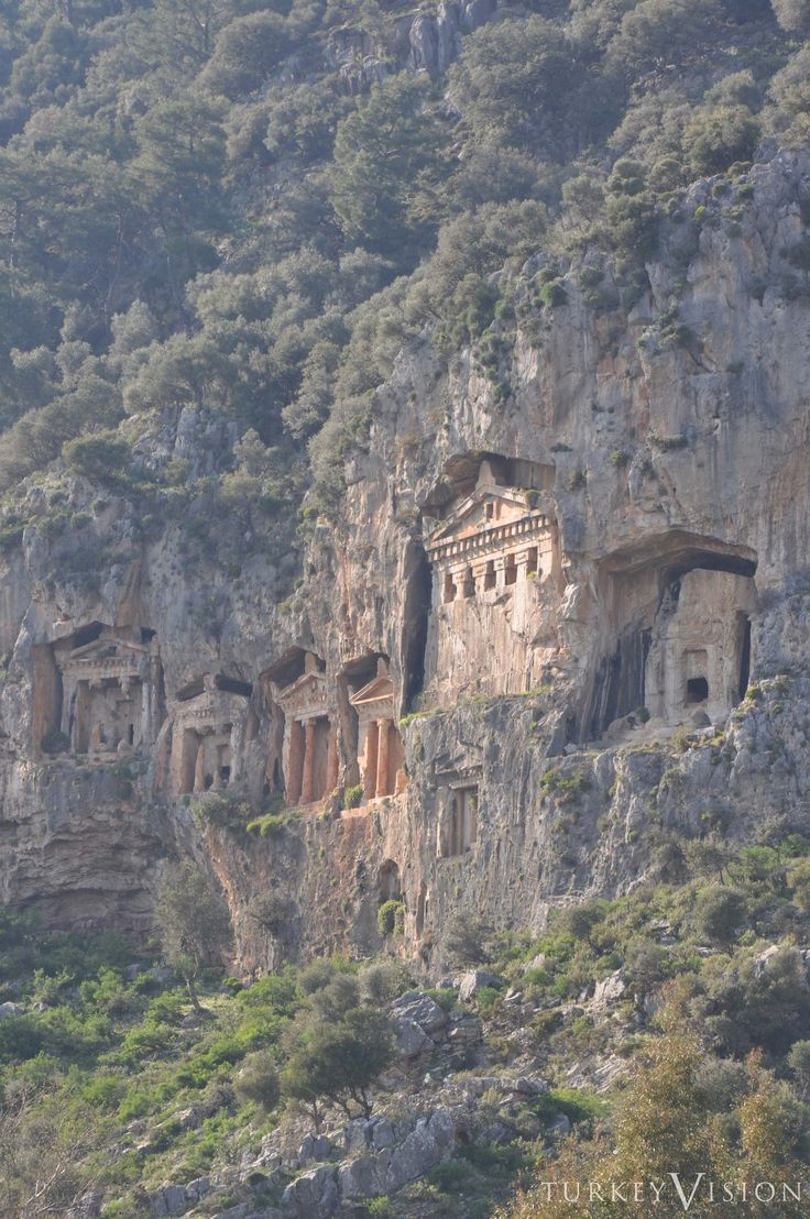 Kaunos Tombs in Dalyan, Turkey: Six rock tombs on the Dalyan river (4th - 2nd century BC). The facades of the rock tombs resemble the fronts of Hellenistic temples with two Ionian pillars, a triangular pediment, an architrave with toothed friezes, and acroterions shaped like palm leaves.