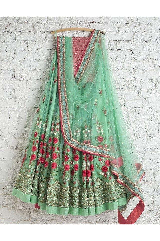 Turquoise lehenga on hanger with pink motifs