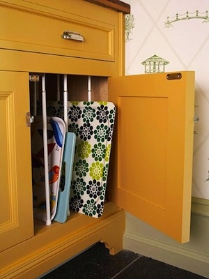 Use tensioning rods in a vertical application to provide divided storage for large items be it trays, cutting boards, or art canvases.