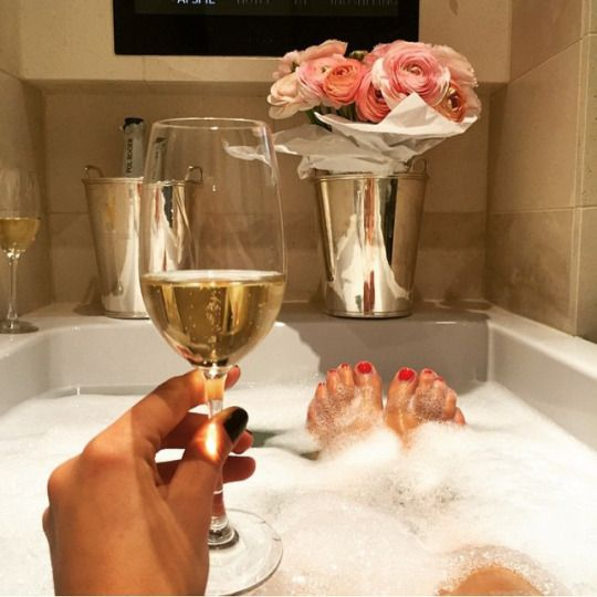 Glamorous women love to luxuriate in a bubble bath with a glass of champagne and beautiful flowers....