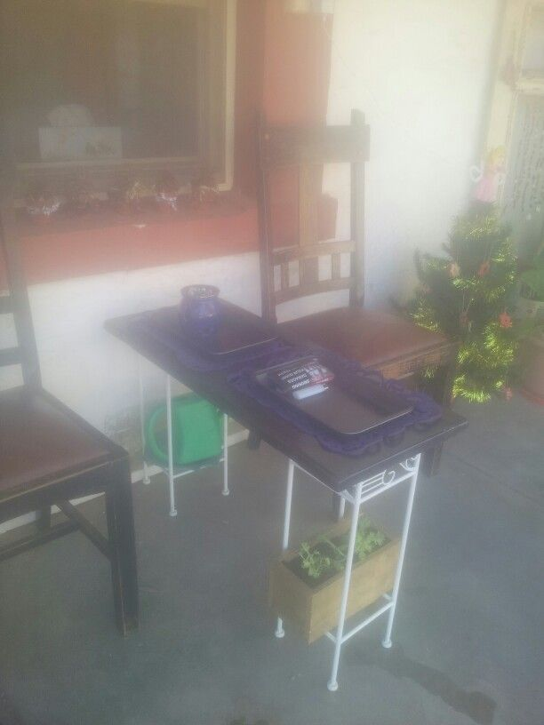 Upcycled cupboard door into table. Baking tray inserts.  Plant stands for legs with planter/gardening tools underneath.