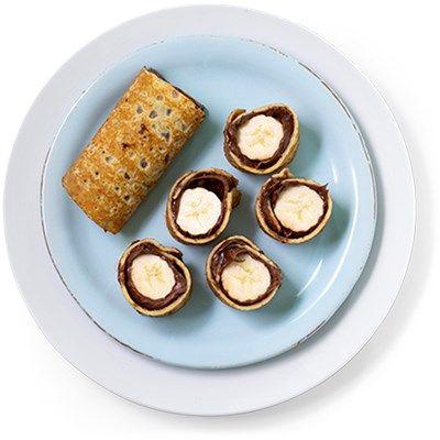 Pannekaker med sjokoladepålegg og banan er verdens beste snacks eller dessert. Rull sammen og del i små sushibiter! Oppskrift på pannekaker med sjokolade.