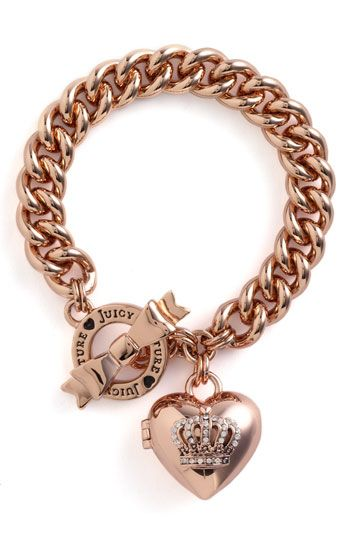A heart locket topped with a sparkly pavé crown dangles from a shiny bracelet finished with a logo-etched ring and adorable bow toggle.