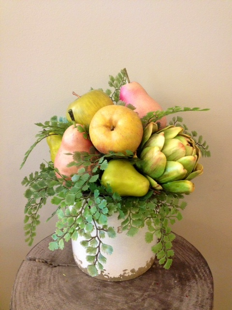 Custom floral arrangement in white ceramic pot with maiden hair fern and fruit including: pears, applies and artichokes.