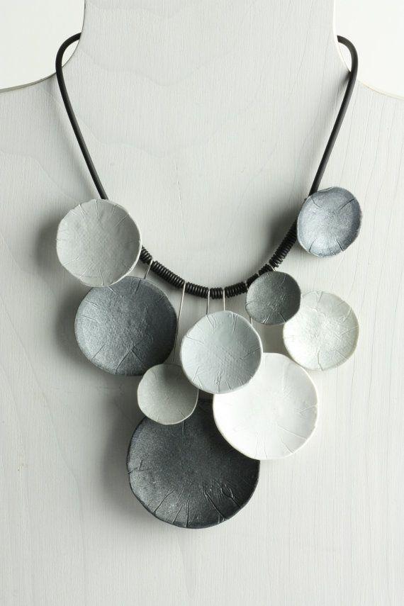 """Cada disco cóncavo del polímero es un tono de gris diferente. Algunos tiene una madre de perla brillo. La pieza del polímero está conectada a un cable de acero inoxidable que cuelga de un 18 """"cordón de caucho con broche de plata."""