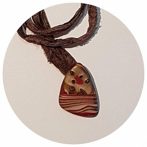 Polymer clay necklaces all individually crafted by hand in Western Australia.  Clay pendant on raw silk. Length approx 35cm. This ethnic inspired pendant is bronze and red in colour and is made using the mukame gane technique. NB. All of my pieces are handmade, orders are shipped 5-10 business days from date of your order. If you need your order for a special occasion, please allow enough time to have it made.  Custom orders are more than welcome. For more information, please email…