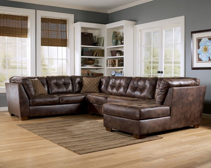 Appealing Living Room Furniture with Wooden Flooring and Grey Wall Paint Color and U Shaped Brown Leather Sofa Set feat Small Brown Fabric Pillows and White Wooden Bookshelf