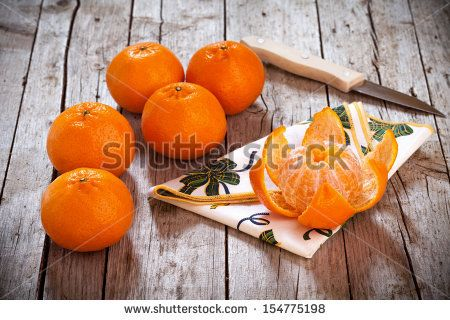 Honey tangerines whole and one peeled, on antique wooden table. - stock photo