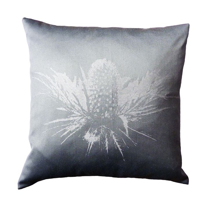 The dramatic sketching's of the Thistle print has been reworked within this cushion to create statement. Tones of silver have been weaved into the flower to create a striking contrast against the luxury grey cotton.  440mm x 440mm  100% cotton twill front and reverse.  Concealed zip closure.  Duck feather cushion pad.  Signature dust bag included.  Made in the UK.
