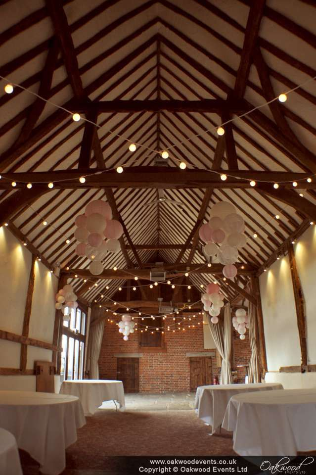 Paper lantern clusters with pink, ivory and lace at the Bix Manor barn for a summer wedding