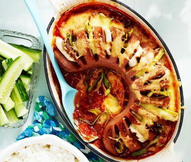 Härligt recept på husmanskost med mumsig falukorv som gratineras och tillagas i ugn. Smarriga ingredienser som tomat, purjolök, dijonsenap, riven ost och pastasås med basilika ser till att rätten får sin imponerande smak! Falukorv i ugn med tomat och purjolök serveras med ris och gurka och kan avnjutas vilken dag som helst i veckan.
