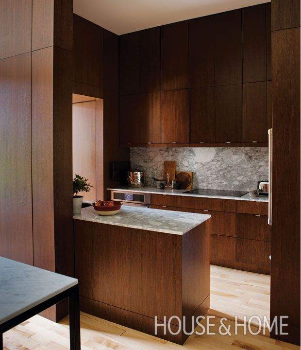 Storage is key in a kitchen. Designers Alexandre Blazys and Benoit Gérard wanted their small kitchen to feel timeless and warm so they brought in rich wood cabinets and millwork that extends to the ceiling, helping elongate the space. | Photographer: Jean Longpré | Designer: Blazys Gérard