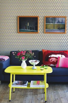 Love the pop of the yellow table against the patterned wallpaper and dark sofa