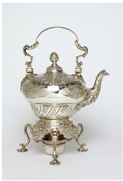 This tea kettle and stand is a fine, example of early Rococo decoration by an English Goldsmith, George Wickes. Made 1740s The Rococo came from France and was first adopted for silver by Huguenot goldsmiths, like Paul de Lamerie, working in London. The sea shells, scalework and scrolls of the decorative design are features of the style.  A tea kettle and stand was one of the most expensive items in the tea equipage often costing over £30