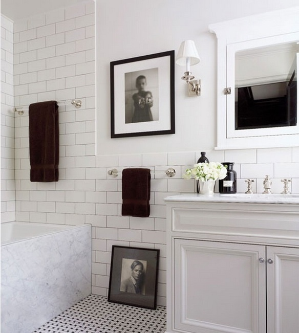 White and black bathroom with black & white photos as art! Also love the subway tile flooring.