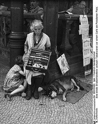Seidenstücker, Friedrich: Eine blinde Straßenhändlerin verkauft Tabakwaren vor einem Café am Potsdamer Platz., 1934 Deutsche Fotothek
