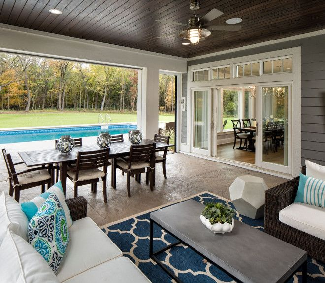 the backyard has a pool and a screened in porch with phantom screens to open to - Inground Pool Patio Ideas