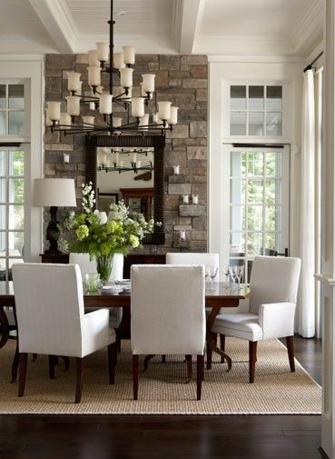 formal dining room in front of house. rock wall in-between two windows in the front of the house. rocks that stick out for ledges. love the lighting.
